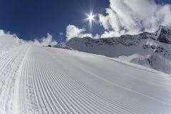 Piste fresche del groomer della neve su una pista dello sci Immagine Stock