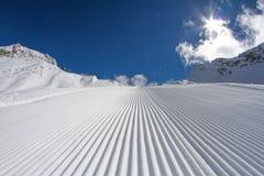 Piste fresche del groomer della neve su una pista dello sci Fotografia Stock