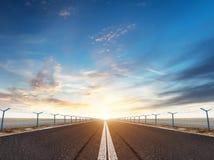 Piste ou route d'aéroport dans la lumière de coucher du soleil de soirée Photo stock