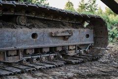 Piste sporche di vecchia fine dell'escavatore su fotografia stock