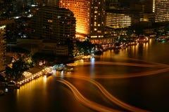 Pistes de bateau sur un côté de fleuve près d'un hôtel la nuit. Images libres de droits
