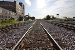 Pistes de train le long des zones industrielles Photographie stock