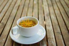 Pistilo da flor amarela do algodão de seda em um copo do chá em cerâmico Imagens de Stock