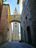 In the streets of Italy: Pistoia bell tower. Bell tower pistoia cathedral view from below under romantic tuscany arch in narrow street, Italy. blue sky sunny Stock Photos