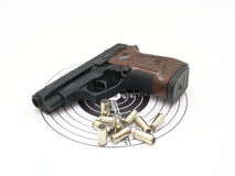 Pistol. The pistol with the brown handle with a target and cartridges lies on a white background Royalty Free Stock Image