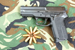 Pistol. A pistol with bullets on a camouflage  background Stock Photo