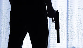 Pistol. A man standing behind a curtain, a pistol in hand Royalty Free Stock Image