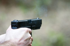 Pistol. Held by the shooter, emitting some smoke after having just been fired Royalty Free Stock Images