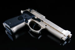 Pistol. The pistol on a black mirror background Royalty Free Stock Images
