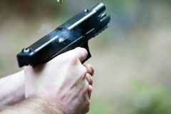 Pistol in Action. Pistol fire caught in action! The slide is back, revealing the next bullet to enter the chamber. There is some smoke, too. Just barely in the Royalty Free Stock Photos