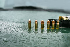Pistol Ammo On Hood. Row of a pistol rounds and ammo box on a wet car hood, selective focus outdoor shot Stock Image