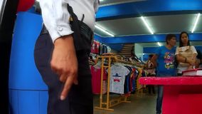 Pistol armed lady security guard on post at a department store. San Pablo City , Laguna, Philippines - August  21, 2015: Pistol armed lady security guard on post stock video footage