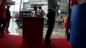 Pistol armed lady security guard on post at a department store. San Pablo City , Laguna, Philippines - August 21, 2015: Pistol armed lady security guard on post stock footage