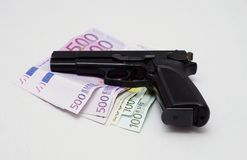 Pistol and banknotes Stock Images