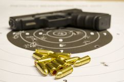 Pistol with bullet on the scorched target.  Royalty Free Stock Photography