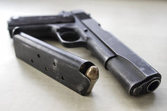 Pistol and bullets. Pistol M1911 laying on table Royalty Free Stock Images