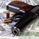 Pistol with bullets on dollars Royalty Free Stock Photos