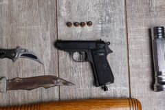 Pistol with a knife on a wooden table stock images