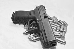 A pistol with bullets shot in black and white. A semi-automatic pistol laying on a pile of bullets with a white background, shot in black and white Royalty Free Stock Photo