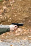 Pistol, Fired. Pistol held by shooter, just fired. Some light smoke is seen exiting the end of the barrel. The brass bullet shell / casing can be seen flying Royalty Free Stock Image
