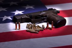 Pistol on flag in the spotlight. Royalty Free Stock Image
