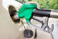 Pistol grip filling car tank with gasoline Stock Photo