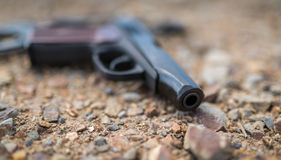 Pistol on ground. Stock Photos