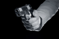 Pistol in hand. On a black background Royalty Free Stock Photos