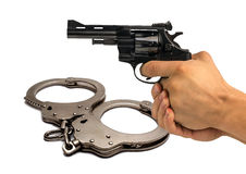 Pistol in hand on background police handcuffs. concept of justic Stock Images