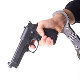 Pistol in hand with handcuffs Royalty Free Stock Photos
