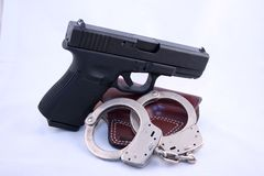 Pistol with handcuffs. Black pistol with leather holster and handcuffs against a white background Stock Image