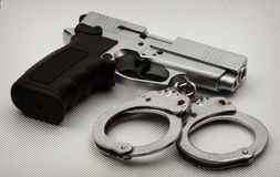 Pistol and handcuffs Royalty Free Stock Photos