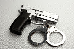 Pistol and handcuffs Royalty Free Stock Photography