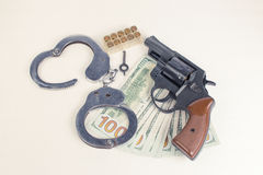 Pistol, handcuffs ammunition and money. Stock Photos
