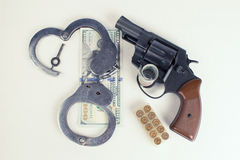 Pistol, handcuffs ammunition and money. Stock Photography