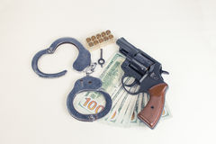 Pistol, handcuffs ammunition and money. Stock Photography