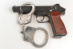 Pistol with handcuffs on gray background Stock Images