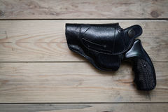 Pistol in a holster. On a wooden table Royalty Free Stock Photo