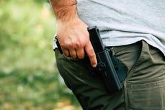 Pistol i pistolhölster Skyttdreven Förbereder sig att skjuta på målet Arkivbilder