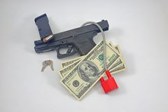 Pistol with lock, ammo and cash royalty free stock image