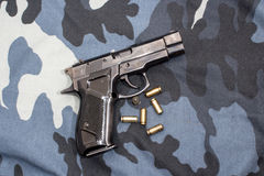 Pistol lying on a camouflage Stock Image