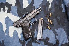 Pistol lying on a camouflage Stock Photos