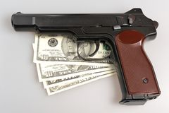 Pistol and money on gray. Background Stock Photos