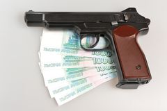 Pistol and money on gray. Background Royalty Free Stock Image