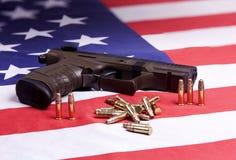 Pistol och ammo på flagga. Royaltyfri Foto