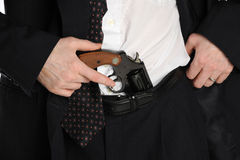 Pistol in pants. Close up of a man's waste, with his hand reaching for a pistol tucked into his pants Royalty Free Stock Images