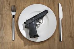 Pistol on plate Stock Image