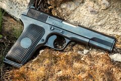 Pistol on the rock background. Black 9mm pistol on a background of stones and moss Royalty Free Stock Photos