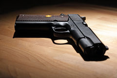 Pistol on the table. M1911 pistol on the wooden table. Shallow DOF Stock Images