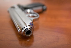 Pistol on a table. Silver pistol lies on a table Royalty Free Stock Photography